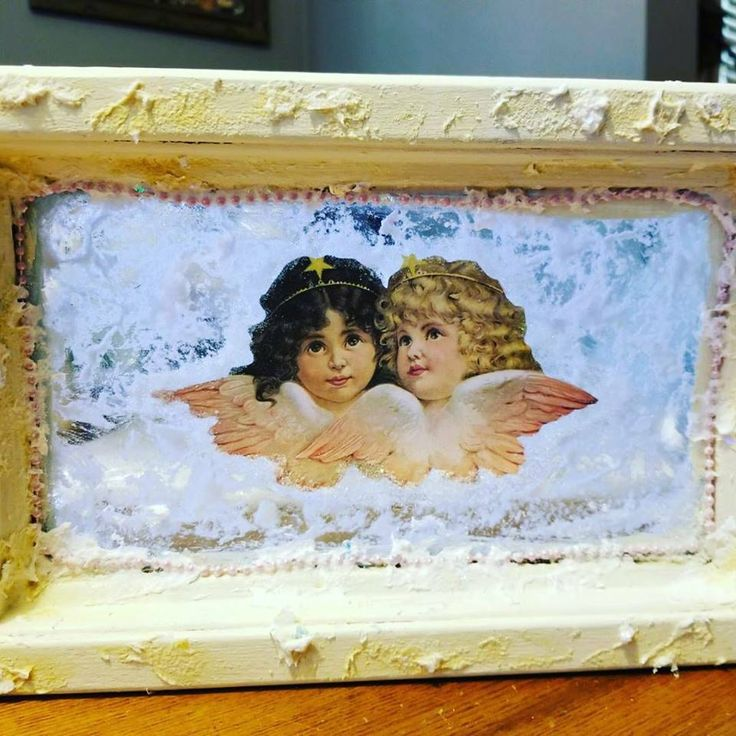 Vintage window insert painted with Buttercream, decorated with Victorian angel images, snow, German glass glitter and beading. By: Claire Matthew #dixiebellepaint #bestpaintonplanetearth #chalklife #homedecor #doityourself #diy #chalkmineralpaint #chalkpainted #easypeasypaint #makingoldnew #whybuynew #justpainting