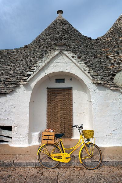 A bright yellow bicycle in front of a trulli (cone roofed building) in Alberobello, Italy ~ photo by Lee Duguid
