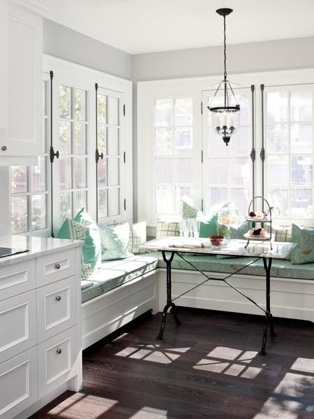 Breakfast nook with built in banquette seating love the white cabinets and built ins love the floors and cushion color not so much the table