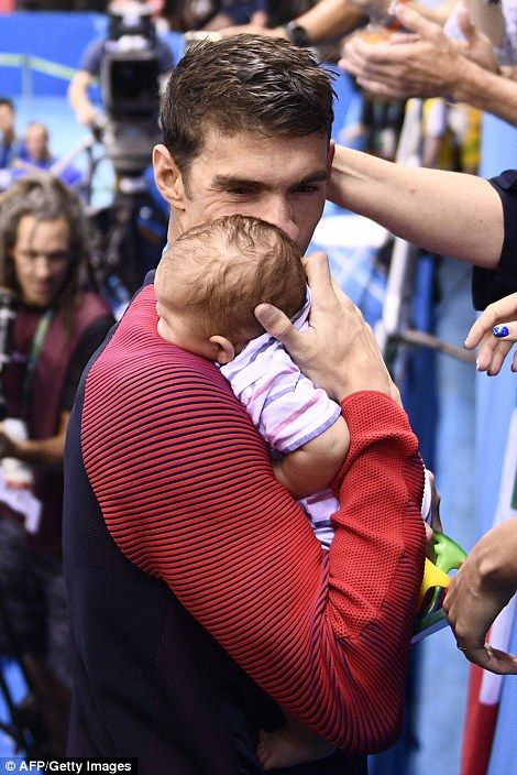 Phelps went to the stands to share a tender moment with his baby son Boomer (left) and fiancée Nicole Johnson