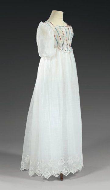 Girl's dress, circa 1810. Robe de jeune fille, époque Empire, vers 1810, fine gaze de coton diaphane, taille haute serrée par un lacet, plastron en broderie anglaise cernée d'un biais de soie rayée bleu et rouge, manches ballon et bas de jupe cranté en broderie blanche. ThierrydeMaigret