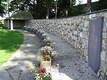 The memorial of the Malmedy massacre at Baugnez. Each black stone embedded into the wall represents one of the victims.