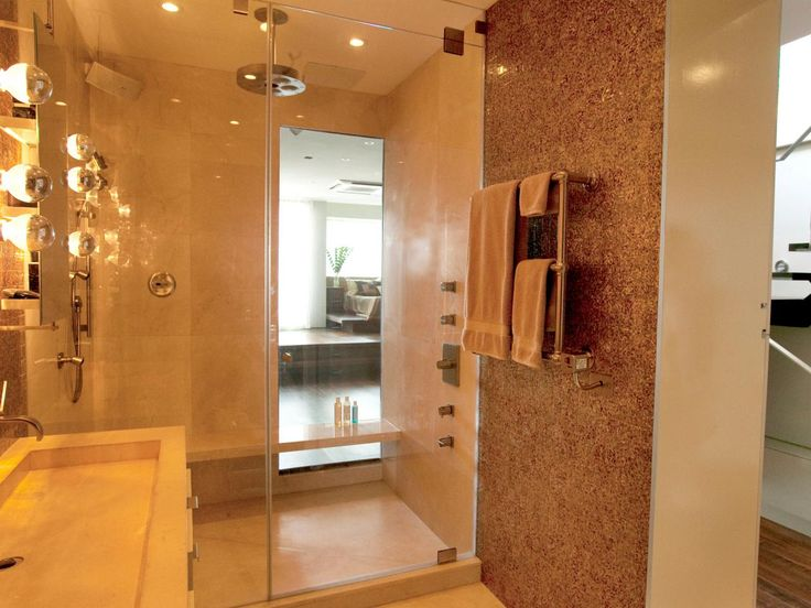 A beige color scheme accented by glass and recessed lighting brings elegance to this master bathroom. A large shower, shower bench and towel warmer make this a luxurious spot for the masters of the house.