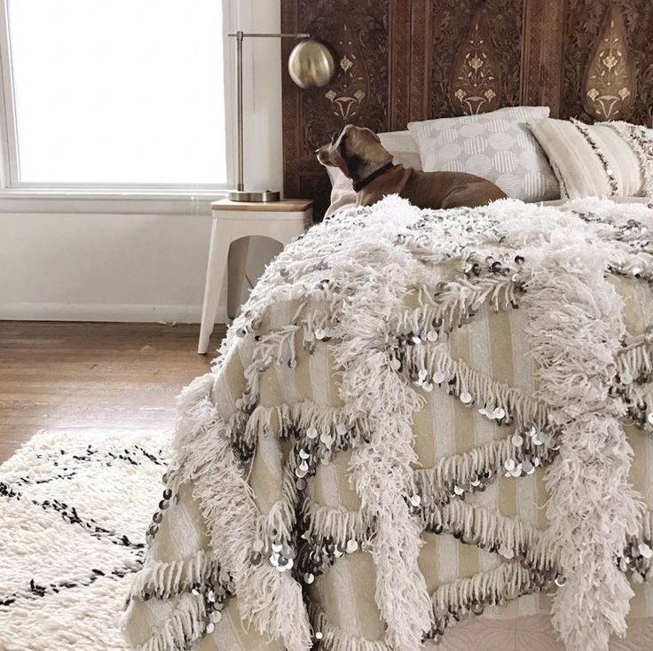 Global chic style in a neutral bohemian bedroom featuring an inlaid carved wood folding screen as a headboard, a Moroccan wedding blanket on the bed and a Moroccan area rug - Eclectic Home Decorating Ideas & Decor - design sponge.com