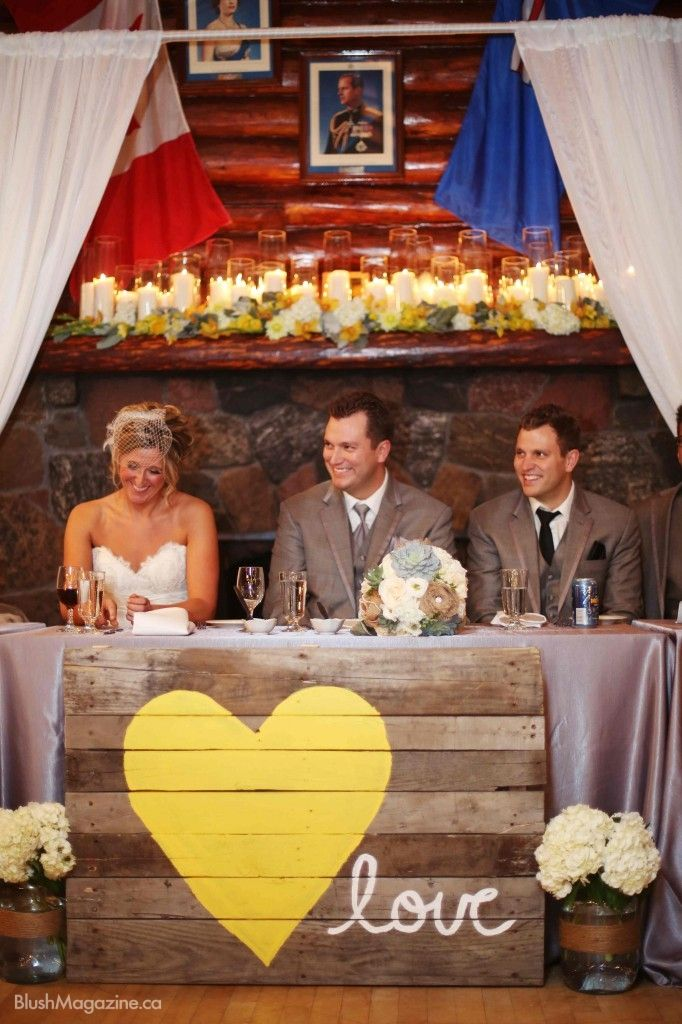 How adorable is this rustic chic head table.  Loving the painted wood sign and candle filled mantel