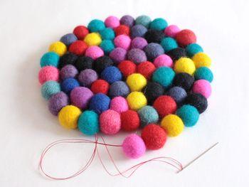 フェルトボールの真ん中に糸を通して、それをくるくると渦巻き状にしていくと完成します。