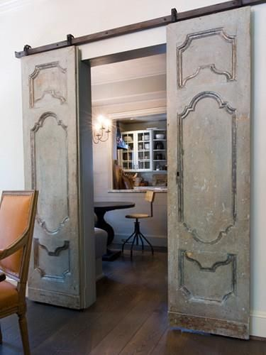 I don't like this faux distressed look, but this door is totally your style. I would use a more stylish/contemporary track with them as well.