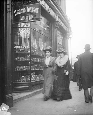 Full-length view of two women, both wearing hats, one wearing fur collar, walking on Grafton St., Dublin, Ireland, c.1890-1910.