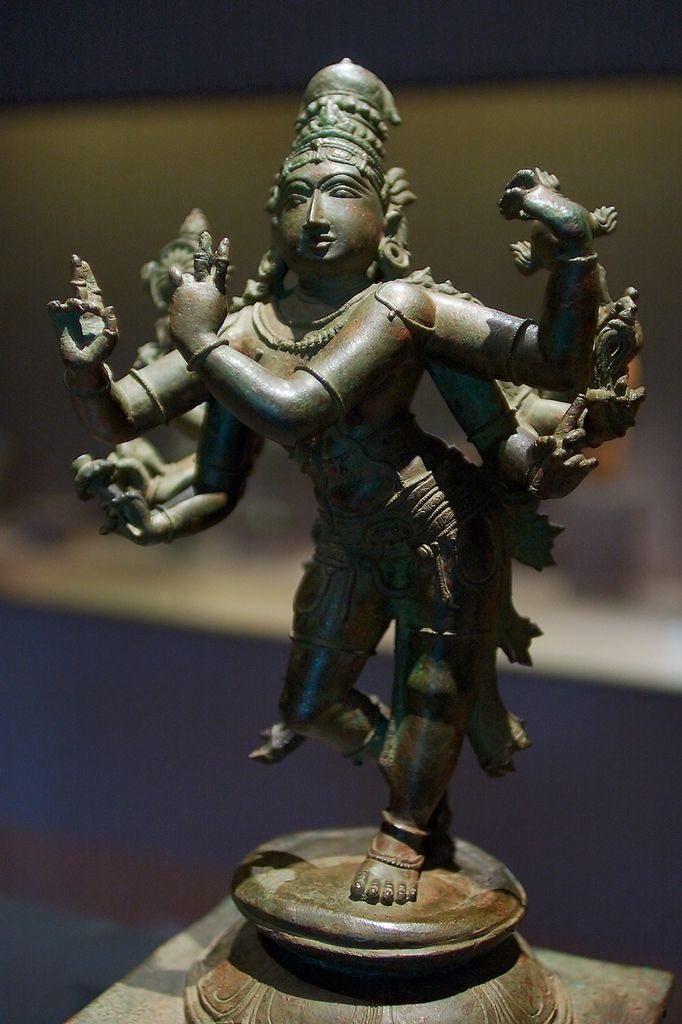 Cosmic Form of Krishna, 15th century, India: Tamil Nadu, bronze.  This ten-armed image of Krishna is an unusual depiction of the god. The wheel and the conch shell in his rear set of hands identify him as an incarnation of Vishnu. His two front hands are positioned as if holding a flute, a common portrayal of a young Krishna. However, the additional sets of arms are not often seen in images made during the reign of the Cholas. It is likely that this figure was made during the reign of the…