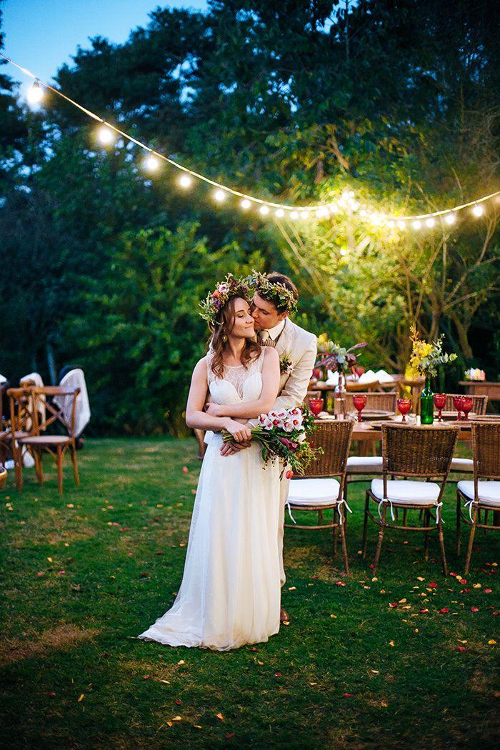 Foto linda com noivos de coroa de flores na cabeça em festa de casamento ao entardecer com fio de luzes.