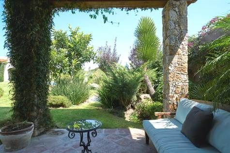 Outdoor terrace with stone columns and view to gardens of Mission Revival house in San Miguel de Allende #agavesanmiguel #sanmiguelrealestate