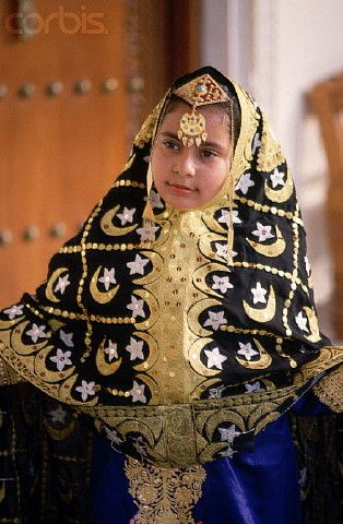Bahrain   A young girl models a black chador, embroidered with gold thread, and ornamental hair jewelry at the Heritage Center in Manama.   © Adam Woolfitt/Corbis