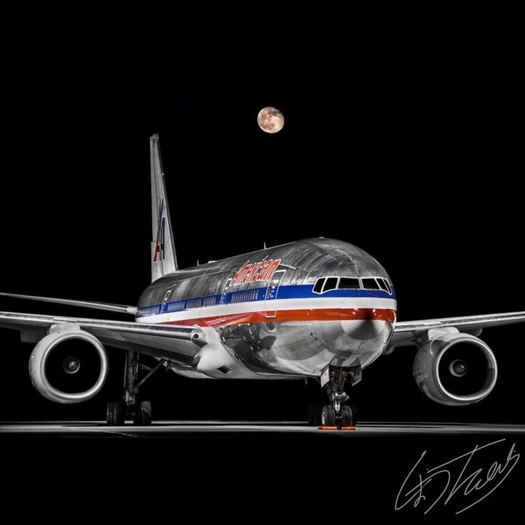 Boeing 777 that shows how aircraft proportions are so similar no matter the size. It looks like it could be a 737 (actually similar size fuselage to the engines shown) or 767 except for the barely visible triple bogies on each side and door placement. A wonderful shot with the moon!