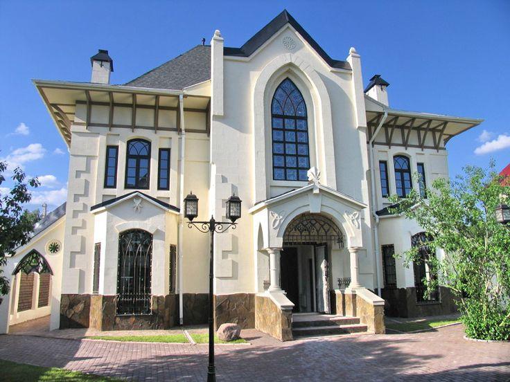 Внешняя отделка штукатурного загородного дома белого цвета в готическом стиле с рустами