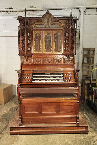 An 1890's, Gothic Style, K.A. Andersson 3 Keyboard Pedal Organ at Besbrode Pianos £45,000. Cabinet Features Elaborate Carvings of Cherubs Playing Musical Instruments, Trefoils, Quatrefoils, Tracery, Foliage and Mythical, Dragons Adorning Candle Holders. The Arcading Features a Central Pointed Openwork Lancet Covered with Fabric Painted with Archangels.