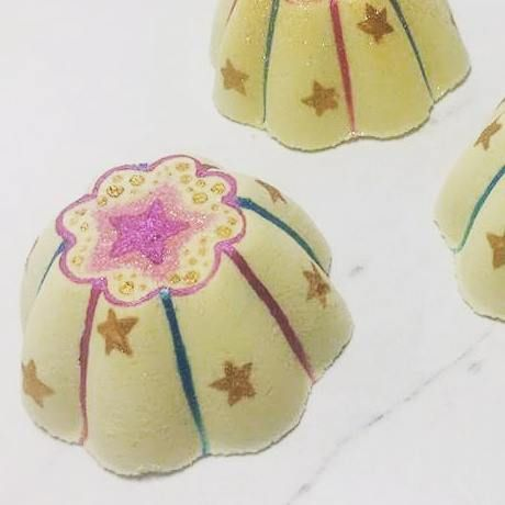 This 100% vegan bath bomb spins around in the bath, releasing blue stripes of color from within! Stunning both before and after it's in the water. Handcrafted and hand painted with stars all over its adorable cake shape.