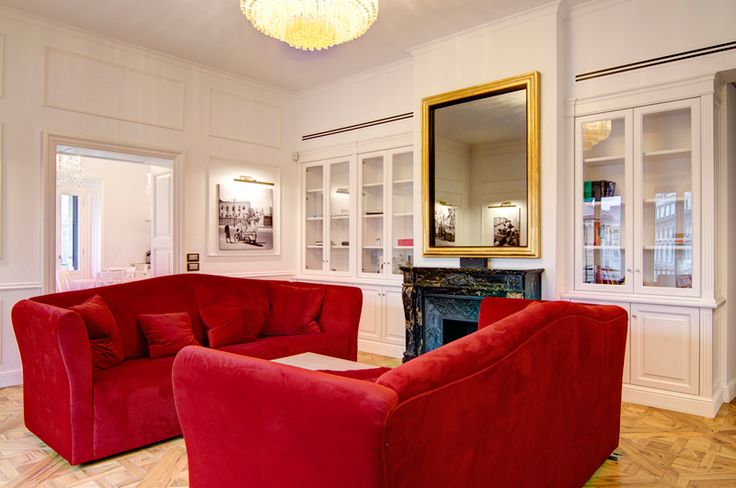 A classy chic apartment in central Milan by Nomade Architettura http://www.nomadearchitettura.com/#all  red velvet custom made sofas, timber floor, black and white pictures, photos, tv mirror, white custom made book case, venician murano chandelier