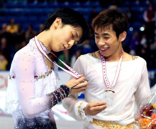 スケートカナダで2位に終わった羽生結弦(左)は表彰式の後、3位の織田信成とメダルを見つめた=川村直子撮影
