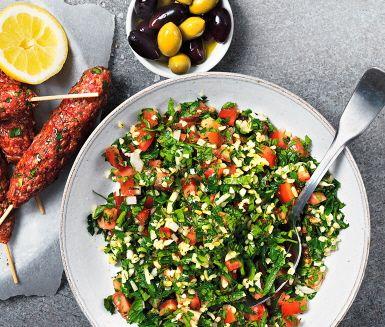 """En sallad med mycket persilja som smaksätts med lök, hackade tomater och lite bulgur. Ringla över olivolja och färskpressad citronjuice. Grön och välsmakande sallad som passar utmärkt till grillat eller på en buffé. Namnet betyder """"lite kryddigt"""" på arabiska men smakar mer än namnet föreslår."""