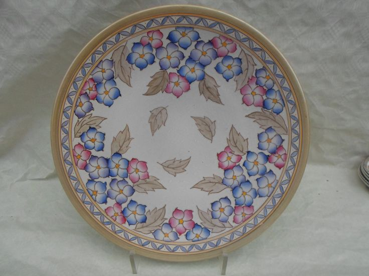 A 1940s HJ Wood Bursleyware charger, designed by Charlotte Rhead in the TL4 pattern, having a tube-lined decoration of pink and blue open flowers with brown leaves on an ivory ground, printed and tubed marks verso, 36.5cm diameter