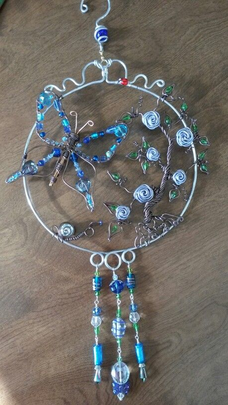 Wire wrapped beaded sun catcher with butterfly and snail, and climbing rose in blue.