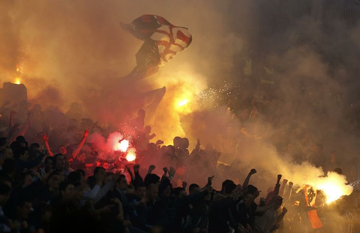 Partizan soccer fans use signal flares and flags to cheer their team on during a Serbian National soccer league derby match against Red Star, in Belgrade, Serbia, Saturday, April 26, 2014. Thousands of riot policemen have been deployed throughout Belgrade to prevent possible violence during a derby match between bitter rivals Red Star and Partizan.