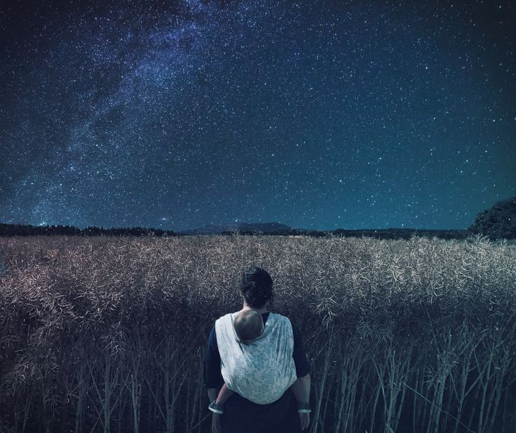 Babywearing mama standing in front of a starry sky and hay field
