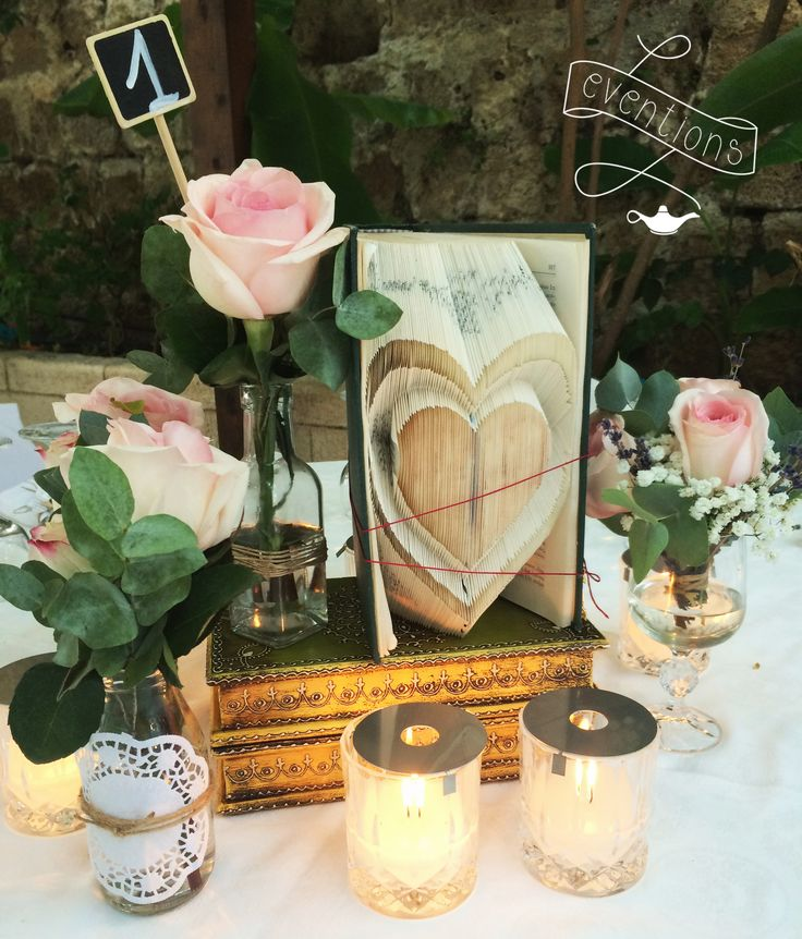 Centerpiece; custom made folded book, pink roses, candles in crystal glasses. Wedding planning & styling in Rhodes, Greece