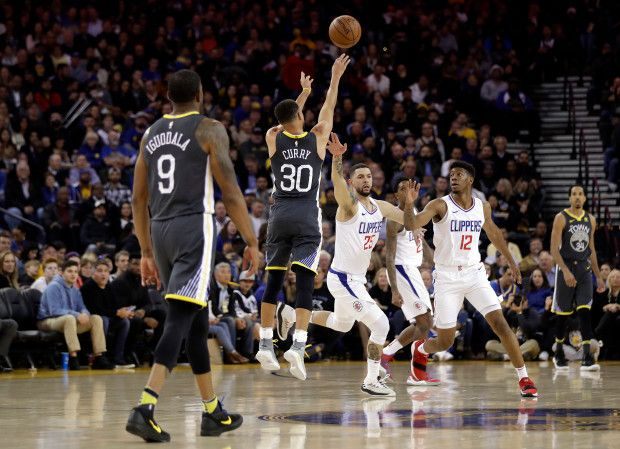 Golden State Warriors' Stephen Curry (30) makes a 3-point buzzer-beater over Los Angeles Clippers' Austin Rivers (25) and Tyrone Wallace (12) to end the first quarter of an NBA basketball game Thursday, Feb. 22, 2018, in Oakland, Calif. (AP Photo/Marcio Jose Sanchez)