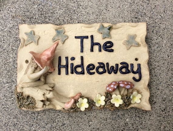 I make this house name plaque from stoneware clay and stoneware glazes and fire it in an electric kiln to 1,220 degrees centigrade.  It is frost proof and will not fade in strong sunlight.  The house name plaque is made entirely by hand. I use coils of clay to form the letters to give it a natural, rustic look and I make the little pixie and mushrooms by hand so each one I make is a little different. If you would like me to change the style slightly or change the colours then please just…