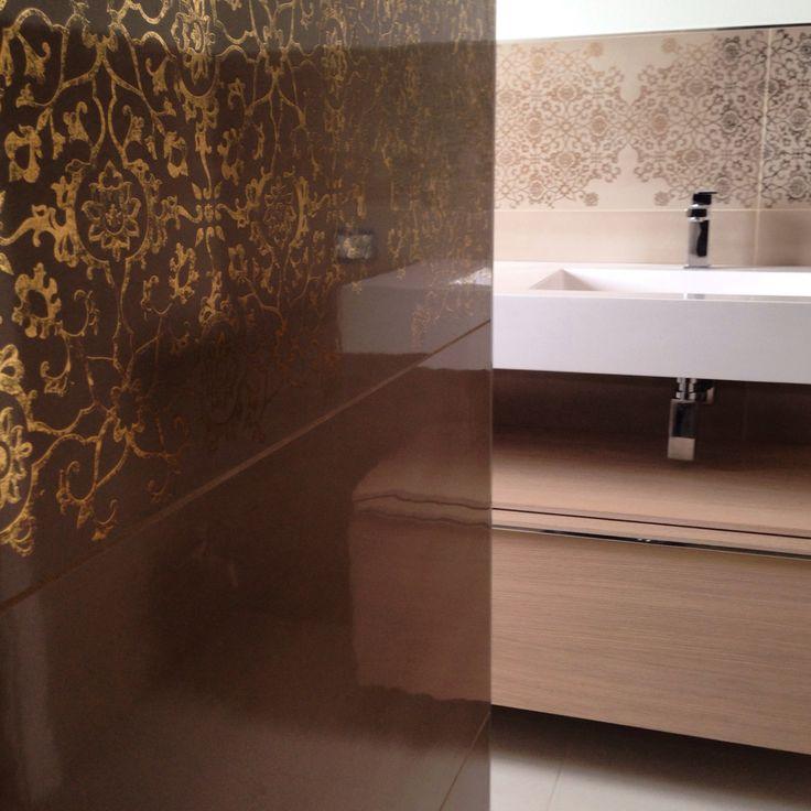 Un rivestimento bagno che ricorda le antiche maioliche fatte a mano, con prezioso decoro dorato dal motivo floreale.