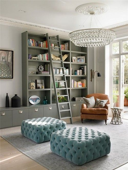 25 Stunning Home Libraries. Messagenote.com Beautiful wall crystal chandelier, ladder in the room, metal side table, tufted poufs, tv on the wall.