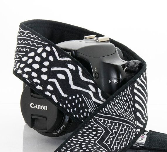 """This dSLR camera strap is done in a black and white tribal style patterned fabric. Each of these will differ somewhat due to the random pattern of this fabric. All cotton fabrics are used on this lightly padded 2 wide strap, available in two lengths and end styles. Back is Outback fabric by Robert Kaufman for comfort and durability. Choose end style, length and pocket options from drop down menu. Scroll down for pocket info.  Length:  Regular is adjustable from 33-46"""" and has a 30"""" fabric…"""