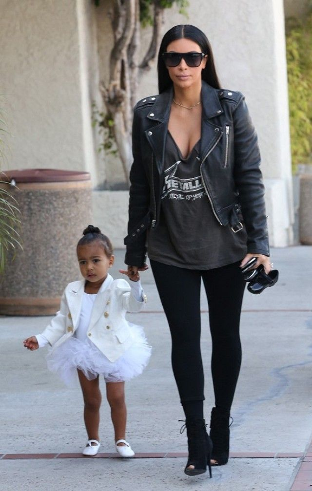 Kim Kardashian wears a graphic t-shirt with a black leather jacket, leggings, and black peep-toe boots.