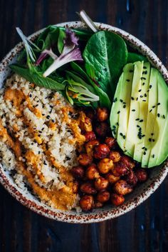vegan buddha bowl - fluffy quinoa, crispy spiced chickpeas, and mixed greens, topped with a mouthwatering red pepper sauce
