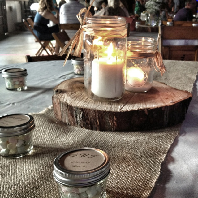 Mason jar centerpieces with candles , wood, and burlap