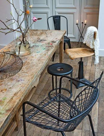 Une table réfectoire marquée par le temps et qui devient particulière et unique confrontée à des chaises au style vintage.