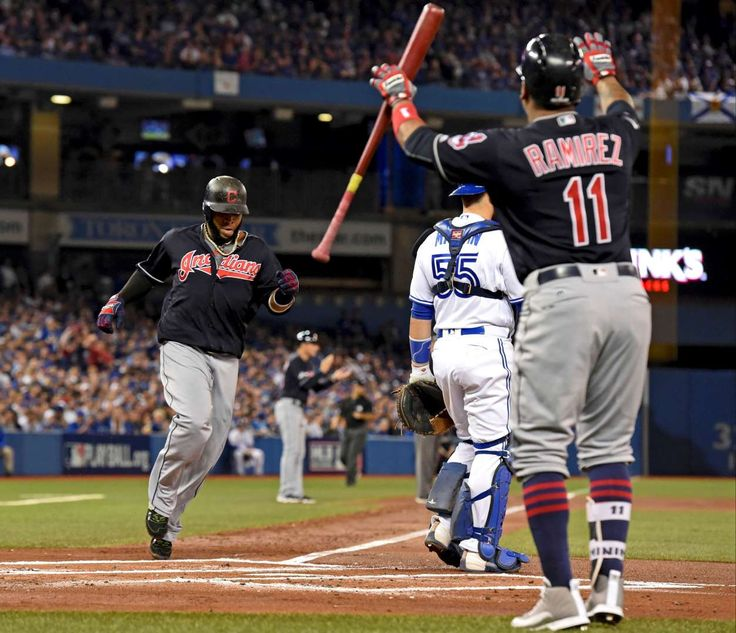 Early score:   Cleveland Indians' Carlos Santana, left, scores on Mike Napoli's RBI double against the Toronto Blue Jays during the first inning in Game 3 of baseball's American League Championship Series on Oct. 17 in Toronto.