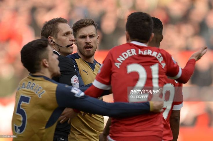 Referee Craig Pawson (2L) intervenes in a confrontation between Arsenal's Welsh midfielder Aaron Ramsey (C) and Manchester United's Spanish midfielder Ander Herrera (2R) during the English Premier League football match between Manchester United and Arsenal at Old Trafford in Manchester in north west England on February 28, 2016. / AFP / OLI SCARFF / RESTRICTED TO EDITORIAL USE. No use with unauthorized audio, video, data, fixture lists, club/league logos or 'live' services. Online in-match…