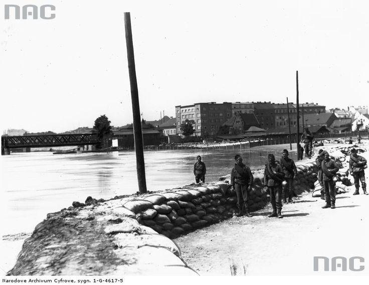 Saperzy układają wał ochronny z worków z piaskiem na placu Na Groblach.