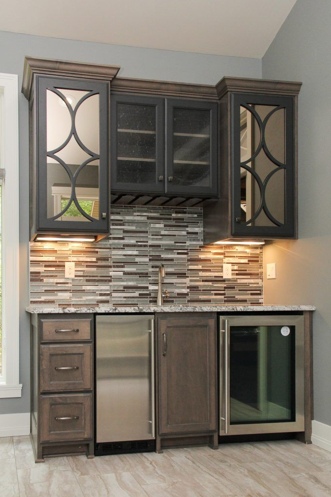 Shades Of Brown And Green Backsplash With Beige Tile Flooring In A Residential Wet Bar