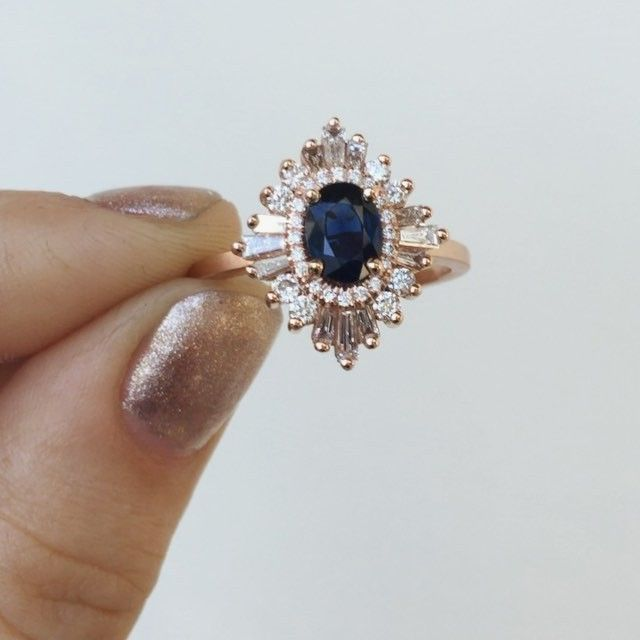 This deep blue, nearly black sapphire is set in a rose gold Oval Gatsby ring with diamonds surrounding This combo is so ! #bluesapphire #bluesapphirering #artdecoring #artdeco #vintageengagementring #vintageinspired #vintagering #engaged #engagementring #rosegoldring #rosegold #righthandring #anniversaryring #cocktailring #uniqueengagementring #uniquering #diamonds #showmeyourrings