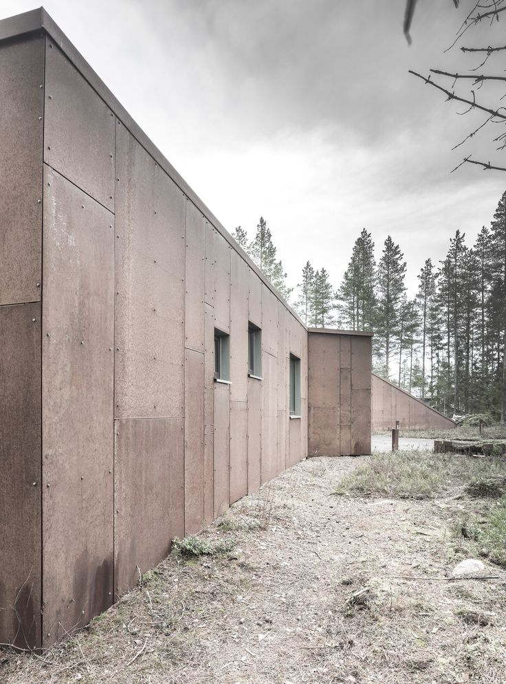 By covering the walls of this house in panels of pre-rusted Corten branded steel and ageing wood, then adding a sloping turf-covered roof, the architects hoped to echo the tones found in the trunks and evergreen foliage of surrounding pine trees.