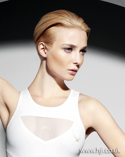 A blonde women's cut with shaved sections on either side was prepped with mousse and blow-dried with the hair directioned away from the face into a quiff.