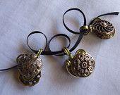 Tre pendenti prodotti con coppie di bottoni gioiello vintage risalenti ai primi anni 60, in metallo, e filo metallico abbinato.