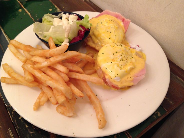Eggs Benedict with fries and salad.