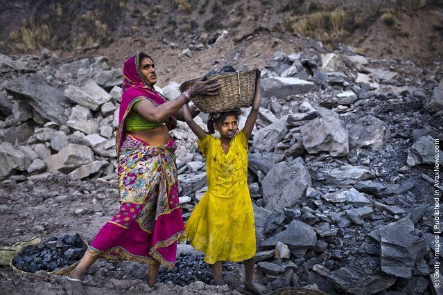 7 year old Soni has a basket of coal lifted onto her head by her mother, 28 year old Savita, after having scavenged coal illegally from an open-cast coal mine in the village of Bokapahari near to Jharia, India.