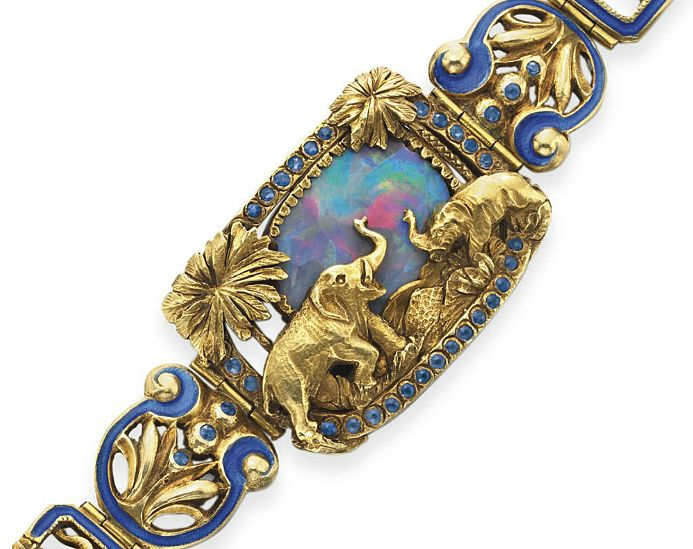 [DETAIL] AN ANTIQUE OPAL, ENAMEL AND GOLD BRACELET   Centering upon a rectangular openwork plaque designed as a desert landscape accented by sculpted gold elephants and palm trees, set against a black opal sky, within a circular-cut sapphire surround, to the similarly-designed gold and blue enamel tapered hinged links, mounted in gold, circa 1900, 7¾ ins.