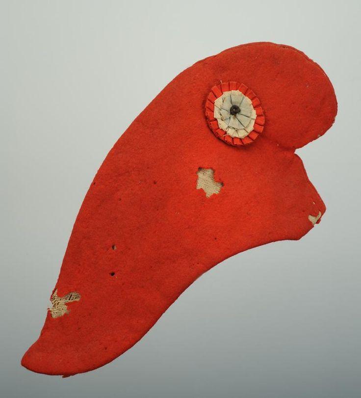 BONNET PHRYGIEN, 19ème SIÈCLE.  Bonnet en drap rouge, hauteur 18 cm, avec sur le côté gauche une cocarde tricolore Ø 5,5 cm.  Très bon état. L'immense majorité des bonnets phrygiens, dits bonnets rouges, évoquant la Révolution, sont des reconstitutions postérieures souvent réalisées pour les dates anniversaire commémoratives de la Révolution Française. De part ces matériaux, le bonnet que nous présentons ici à l'intérêt d'être une reconstitution du 19ème siècle.