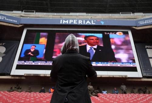 JOHANNESBURG, SOUTH AFRICA - DECEMBER 10:  A spectator watches a telecast of U.S. President Barack Obama as he speaks during the Nelson Mandela memorial service at Ellis Park on December 10, 2013 in Johannesburg, South Africa. Over 60 heads of state have travelled to South Africa to attend a week of events commemorating the life of former South African President Nelson Mandela. Mr Mandela passed away on the evening of December 5, 2013 at his home in Houghton at the age of 95. Mandela became…